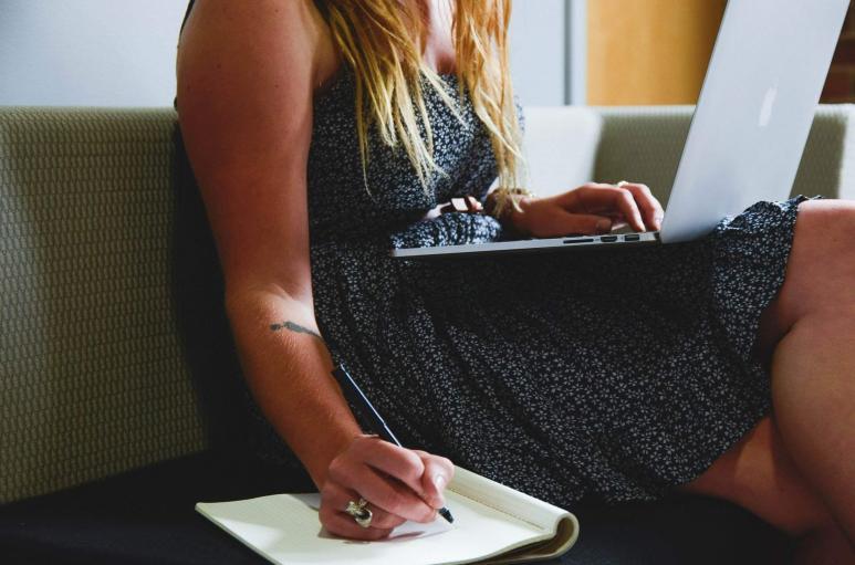 Eine Frau tippt etwas in den Laptop und notiert etwas auf einen Block